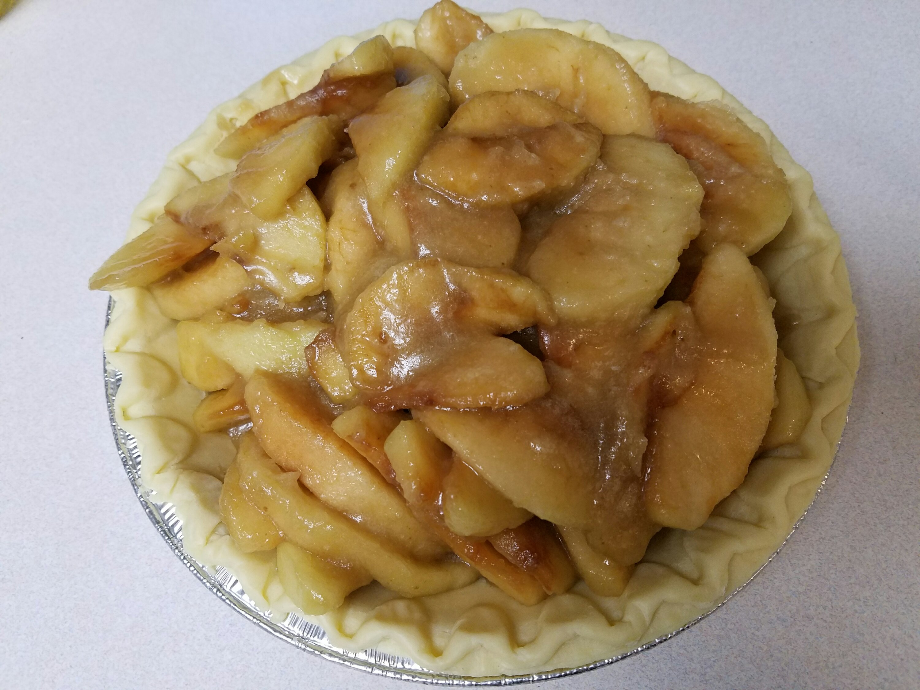 Mounded apple pie filling in tinned crust